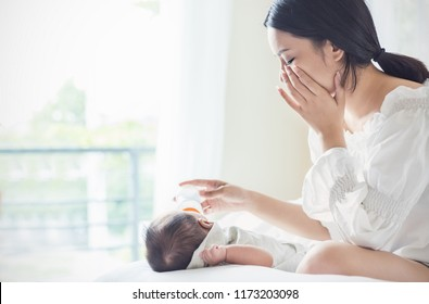 portrait of Asian mother nursery feeding bottle of formula milk to newborn baby in bed crying suffering from post natal depression. Health care breastfeeding single mom motherhood stressful concept.