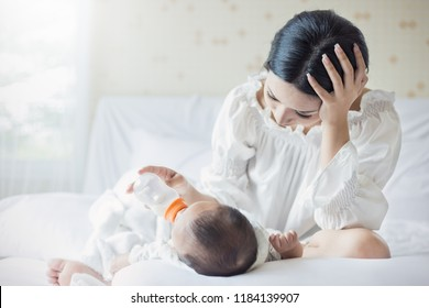portrait of Asian mother nursery feeding bottle of formula milk to newborn baby in bed suffering from post natal depression. Health care single mom motherhood stressful concept.
