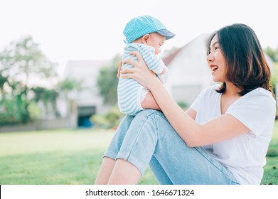 Portrait of a asian mother smiling with her 3 months old baby boy on green grass outdoor in  park.