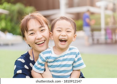 Portrait of asian mother and toddler boy child playing having fun together. Happy son and mom laughing and kissing in playground outdoor.Love family lifestyle single mom.Mother's day holiday concept.