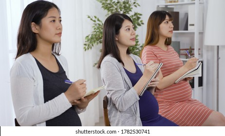 portrait asian mothers-to-be taking prenatal education class with full attention. first-time moms seated in a row nodding head while listening to lectures.