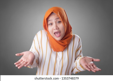 Portrait of Asian muslim businesswoman wearing hijab shows refusal or denial gesture, shoulder shrug, I don't know expression