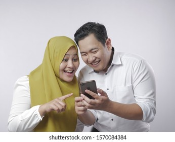 Portrait of Asian muslim couple shocked or surprised to see something on smart phone, happy expression winning gesture
