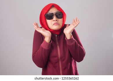 Portrait of Asian muslim lady wearing black sunglasses in red suit and hijab shows refusal or denial gesture, shoulder shrug, I don't know expression