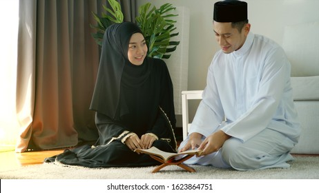 Portrait of an Asian muslim man and woman reciting Surah al-Fatiha passage of the Qur'an in a single act of Sujud called a Sajdah or prostration