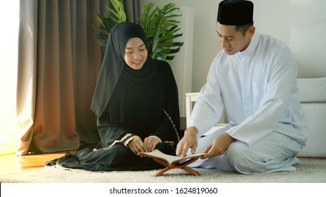 Portrait of an Asian muslim man woman reciting surah al-Fatiha passage of the Qur'an in a single act of sujud called a sajdah or prostration in a daily prayer at home