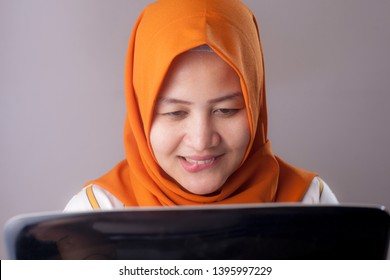 Portrait of Asian muslim woman with naughty passionate expression, biting her lips while watching porn on laptop