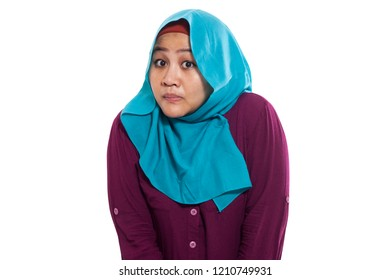 Portrait of Asian muslim woman shrugging shoulder, denial or I don't know gesture isolated on white
