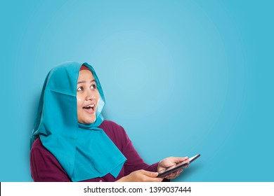Portrait of Asian muslim woman surprised and smiling happy to see something above when using her smart phone with copy space