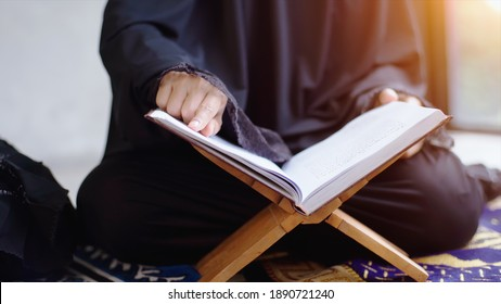 Portrait of an Asian muslim women in a daily prayer at home reciting Surah al-Fatiha passage of the Qur'an in a single act of Sujud called a Sajdah or prostration