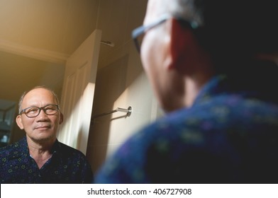 Portrait of Asian old man wear glasses looking his face through mirror in the bathroom, Smiling face.