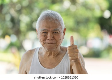 A portrait of asian old retire who has alzheimer's disease. Laughing 80 year old senior man candid portrait very happy when go to park. Funny 80 year's man looking at camera. Concept happy people.