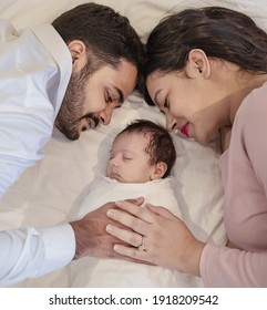 Portrait of Asian parents with newborn baby, Closeup portrait of asian young couple father mother holding new born baby in hospital bed. Happy asia lovely family, nursery breastfeeding mother's day