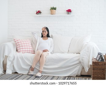 Portrait of Asian pregnant woman has headache sitting on sofa at home in the living room.