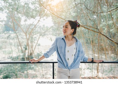 portrait asian in relax holiday with wear jean shirt by smile happy standing outdoor