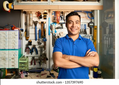Portrait of Asian repairman standing with arms crossed and smiling while standing in workshop with instruments on the wall in the background