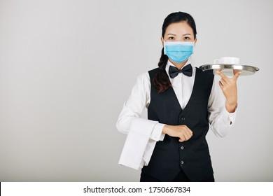 Portrait of Asian restaurant waitress in medical mask serving food