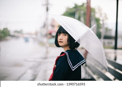 Portrait of Asian school girl walking with umbrella at uraban walkway on raining