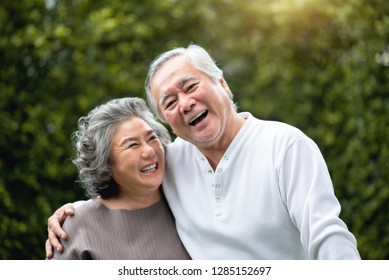 Portrait of Asian Senior Couple in casual laughing over green nature at park outdoor. Happy smiling Elderly man, woman enjoying with positive emotions at garden. People Health care, Family Lifestyle
