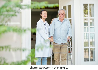 Portrait of Asian senior man with walker walking outdoors together with Asian young nurse he lives at nursing home