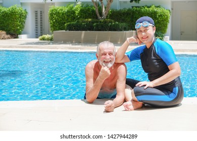 Portrait asian senior woman and caucasian old man resting together in the edge of swimming pool in clubhouse