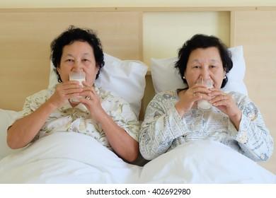 Portrait of Asian senior woman drinking milk on bed