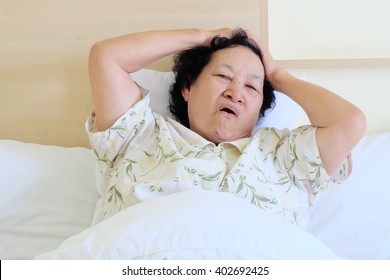 Portrait of Asian senior woman headache on bed