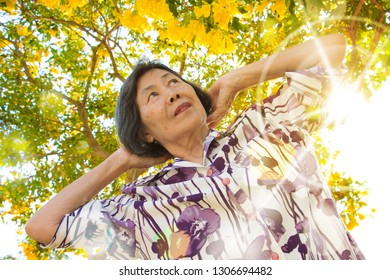 Portrait of asian senior woman ,relaxing under the yellow flowers tree.