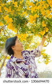Portrait of asian senior woman ,smiling with the yellow flowers.