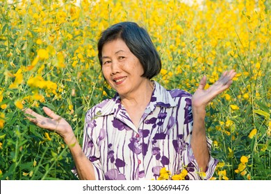 Portrait of asian senior woman ,smiling in the yellow flowers field.