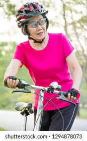 Portrait of asian senior woman wearing helmet ,standing with her folding bike.