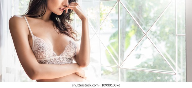 Portrait of asian sexy woman with a delicate skin dressed in white lace underwear bra  sexually staying on a boudoir background. Sexy girl modern lifestyle concept banner