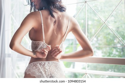 Portrait of asian sexy woman with a delicate skin dressed in white lace underwear bra sexually staying on a boudoir background. Woman try to takeoff her bra. Sexy girl modern lifestyle concept.