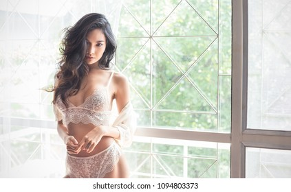 Portrait of asian sexy woman with a delicate skin dressed in white lace underwear bra sexually staying on a boudoir background. Sexy girl modern lifestyle concept.