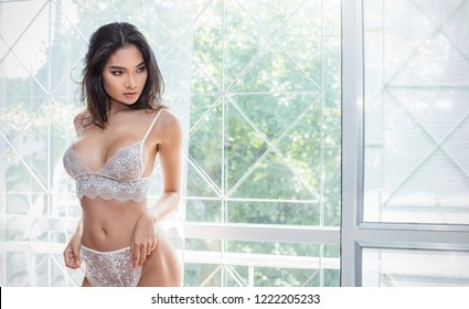 Portrait of asian sexy woman with a delicate skin dressed in white lace bra lingerie underwear sexually staying on a boudoir copy space background. Sexy girl modern lifestyle concept panoramic banner