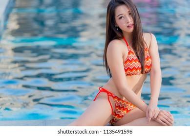 Portrait of asian sexy woman at swimming pool,Thailand has a slim body shape,Healthy woman concept,Fashion bikini summer