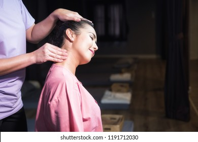 portrait of Asian smile beautiful woman massaging neck by professional massager in spa salon. Girl relax and Body care treatment by Thai massage.