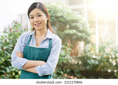 Portrait of Asian smiling woman standing outdoors with green trees in the background