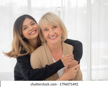 Portrait of Asian teen daughter is hugging her adopted caucasian mother looking at the camera and smile happily with each other. love and sharing time of stepmother, stepdaughter concept