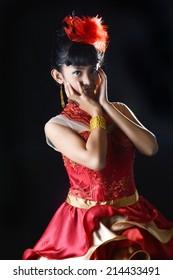 portrait of asian teenage girl dressing glamorous red gold on black background