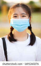 portrait of asian teenager wearing protection mask standing outdoor