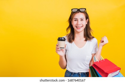 Portrait Asian Thai beautiful happy young woman smiling hold shopping bags multi-color and take away coffee cup her looking to camera, studio shot isolated on yellow background, with copy space