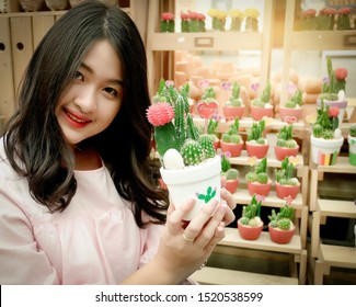 Portrait Asian Thai cute young female girl smile holding beautiful cactus tree in pot with blurred sunset cactus on wooden shelves farm garden background copy space. Pretty teen posting looking camera