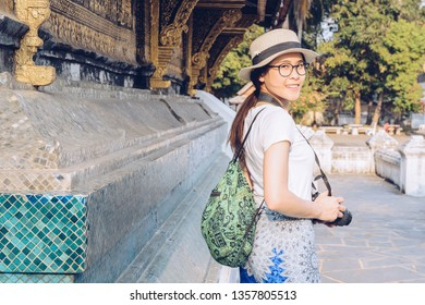Portrait of Asian tourist visiting Wat Xieng Thong an iconic temple in Luang Prabang, the UNESCO world heritage town in north central of Laos. Conceptual of tourist enjoying vacation and holiday.