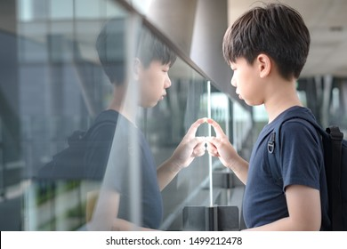 Portrait of an asian tween student boy (12 -15 years old) standing alone lost in thought on the walkway at school. Bullying, Teen problem, Physical or emotional harm, Loneliness, Withdrawn, Introvert.