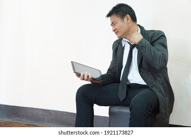 Portrait of Asian unemployed man holding digital smart tablet. Feel serious, worried about finding job from internet website during the crisis  and impact of world bad economy and Covid-19 epidemic.