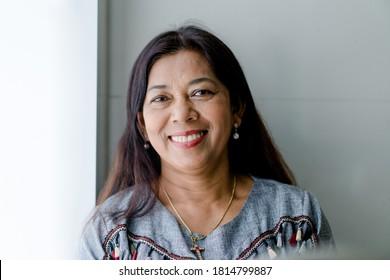 Portrait von asiatischen Frauen 60s lächeln Kamera zu Hause während covid19 coronavirus.Bleiben Sie zu Hause und Lockdown.Senior Christin. Senior Adult Women Lächeln glücklich mit dem Rentenleben.Zahnpflege.