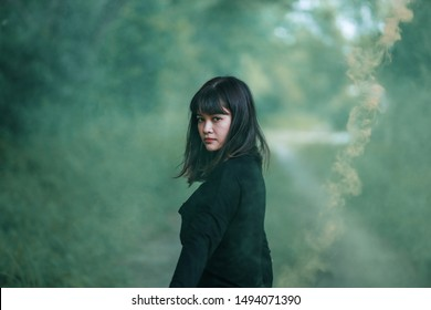 Portrait of Asian woman in black cloth with color fire smoke in forest witch concept