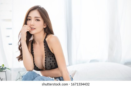 Portrait of asian woman in black lace bra lingerie underwear boudoir. Beauty smiling asian girl just wake up touching skin in her morning routine. Sexy girl in bedroom modern asia lifestyle concept