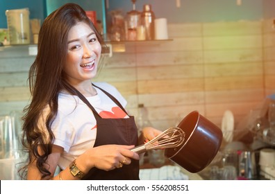 Portrait of Asian woman chef cooking food in kitchen - young attractive smiling woman successful small business owner.